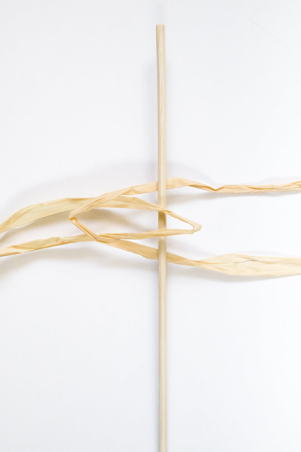 Take another folded raffia piece and tuck the folded end underneath and into the loop. Carefully take the first raffia loose ends and tuck them up into the loop created by the second loop.