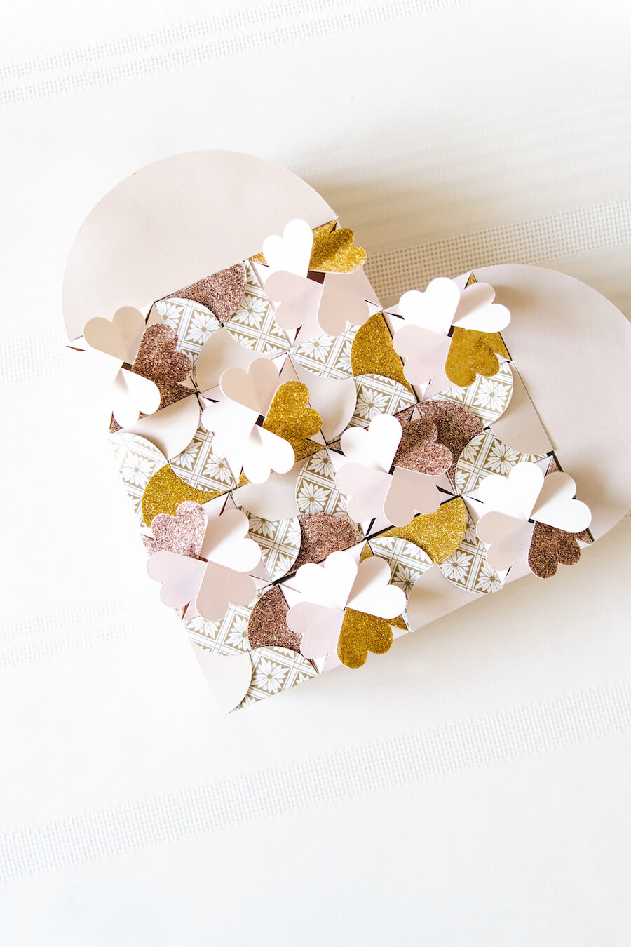 The design of this DIY heart-shaped box is comprised of 15 miniature boxes made from two different (and free!) gift box SVG designs.